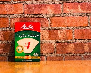 Packaged coffee filters setting on a wood table against a brick wall