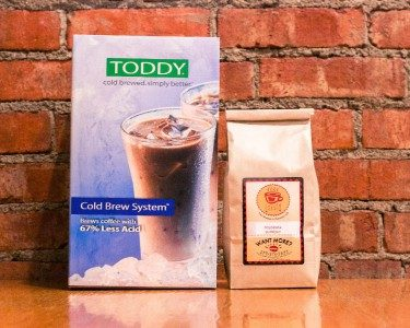 Toddy Cold Brew System packaging setting next to Lakota Coffee Company coffee grounds