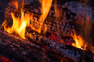 Up close image of yellow flames burning on firewood