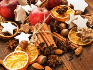 An assortment of cinnamon sticks with orange peels and apples and stars