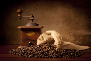 A bag of spilled coffee beans setting next to a cranked grinder
