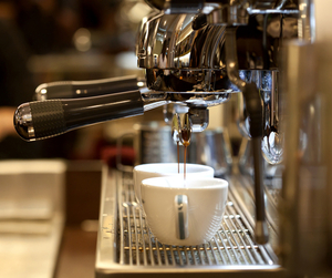 A side view of a cappuccino machine pouring coffee