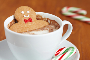 A gingerbread man setting in a cup of coffee