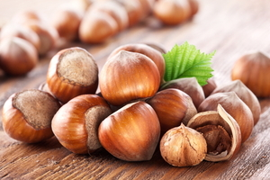 Up close image of hazelnuts piled together on a wooden surface