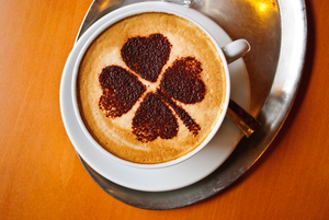 A four leaf clover designed cappuccino in a white mug