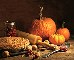 A visual of harvest time objects such as pumpkins, cranberries, nuts and more