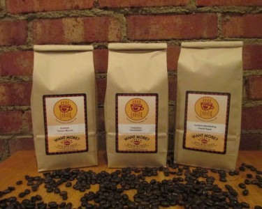 Three bags of Lakota Coffee Company coffee grounds with coffee beans scattered at the bottom