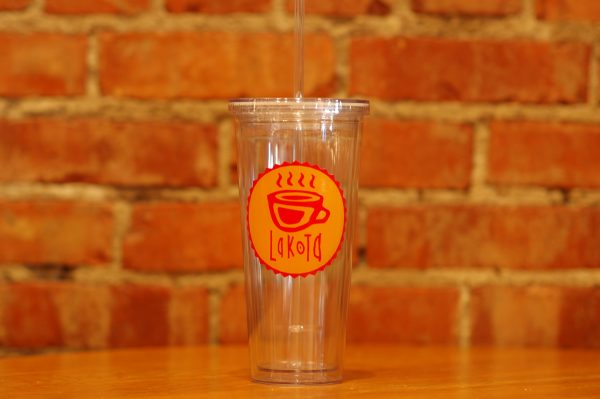 Clear iced tumbler with Lakota Coffee Company's red and yellow label stamped on the front