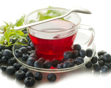Blueberry black tea setting in a glass tea cup surrounded by blueberries