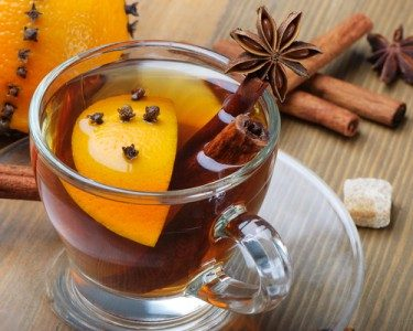 Cinnamon orange herbal tea in a glass mug with a cinnamon stick and orange slice