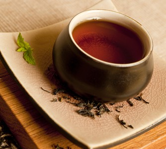 Earl grey black tea in a round ceramic mug setting on a square dish with scattered tea leaves