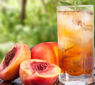 Iced ginger peach black tea in a glass with halved peaches displayed