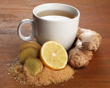 Lemon ginger tea in white mug with lemon slices and ginger pieces surrounding the base