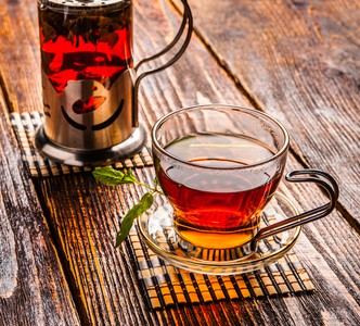 San Francisco black tea in a glass mug positioned by a glass and stainless steal tea diffuser