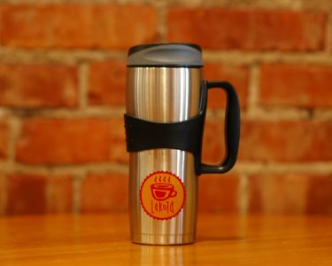 Lakota Coffee Company travel tumbler with black handle setting on a table inside of coffee shop in Columbia, Mo