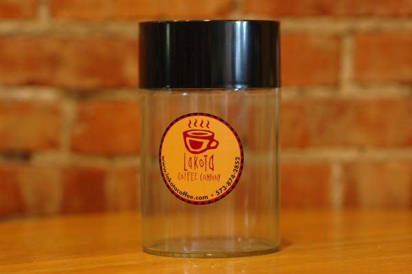Clear container with black lid and Lakota Coffee Company logo