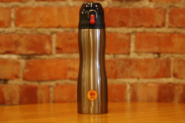 Stainless steel travel tumbler with Lakota Coffee Company logo setting on wooden table