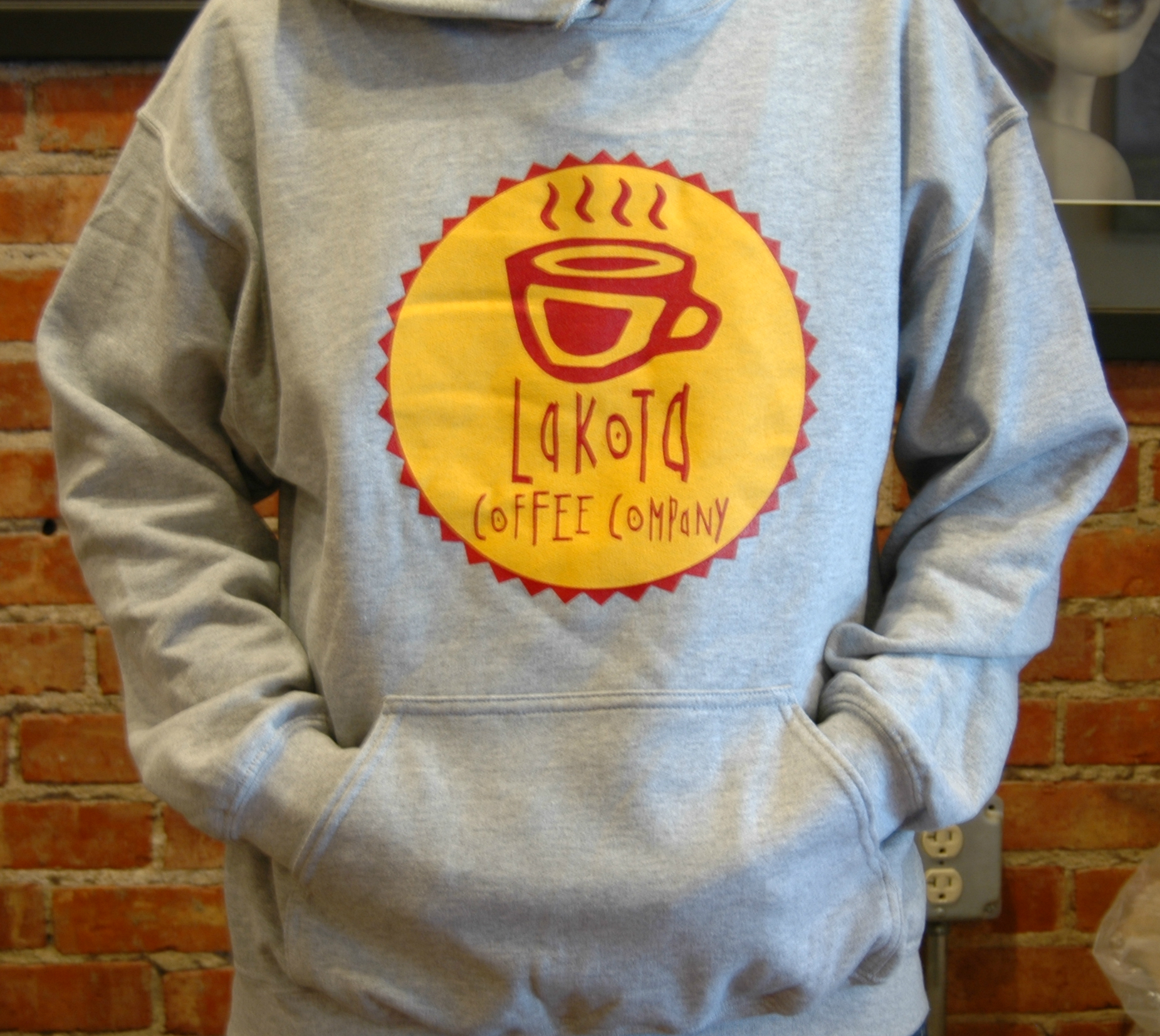 Person wearing a grey hoodie with the Lakota Coffee Company logo on the front in yellow and red