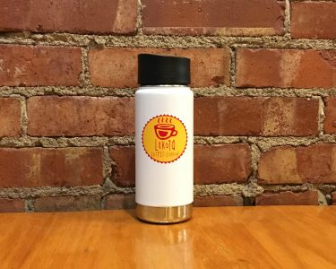 White Lakota Coffee Company water bottle setting on table inside coffee shop
